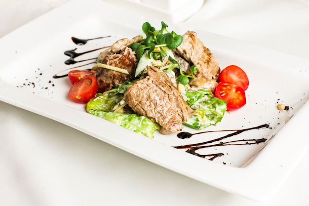 Warm salad with meat, mushrooms, cherry tomatoes, pine nuts and herbs
