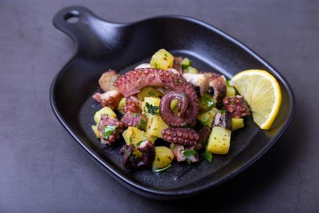 Теплый салат с осьминогом, картофелем и лимоном в маленькой черной сковороде. крупный план, черный фон.