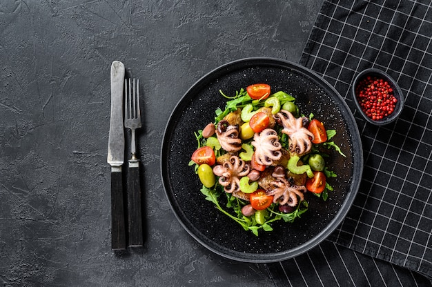 Warm salad with octopus, potatoes, arugula, tomatoes and olives. black background. top view