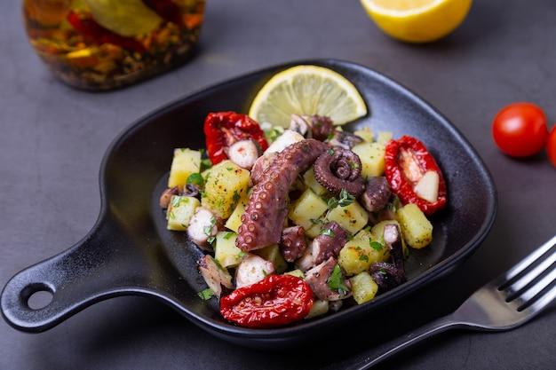 Теплый салат с осьминогом, картофелем, вялеными помидорами, чесноком и лимоном в маленькой черной сковороде. крупный план, черный фон.