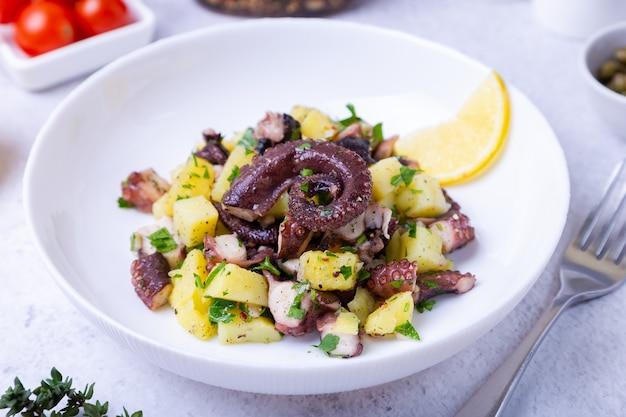 Теплый салат с осьминогом, картофелем, помидорами и лимоном на белой тарелке.