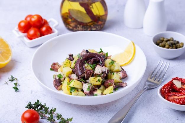 タコ、ジャガイモ、トマト、ケッパー、レモンを白い皿に盛り付けた温かいサラダ。クローズアップ、白い背景。