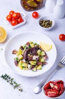 Теплый салат с осьминогом, картофелем, помидорами, каперсами и лимоном на белой тарелке.