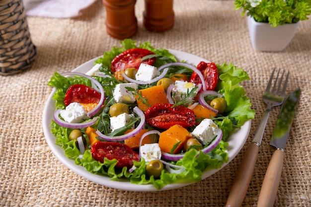 Теплый салат с тыквой, сыром фета, вялеными помидорами, оливками, рукколой и красным луком.