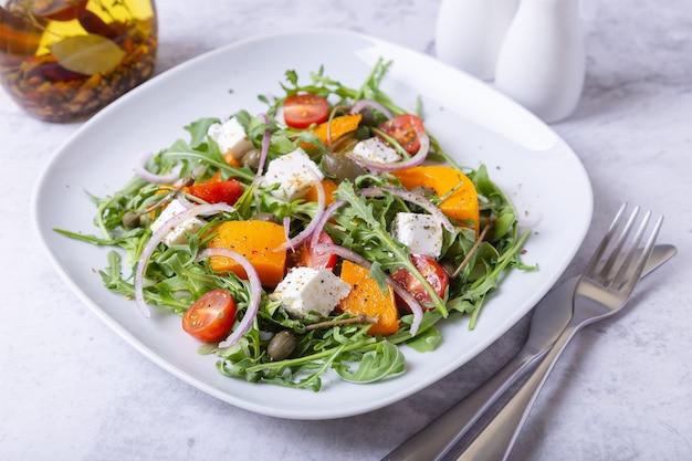 Теплый салат с тыквой, сыром фета, помидорами, каперсами, рукколой и красным луком.