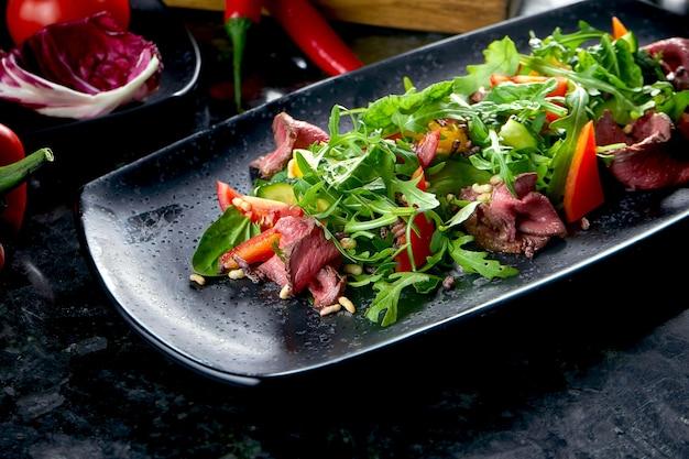 로스트 비프와 신선한 야채를 곁들인 따뜻한 샐러드는 대리석 테이블에 검은 색 접시에 담겨 제공됩니다. 레스토랑 음식. 클로즈업, 선택적 초점