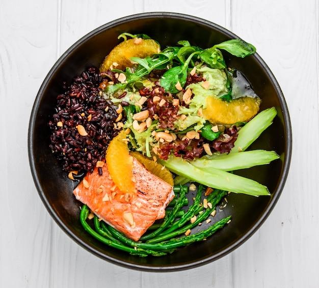 サーモン、ワイルドライス、アスパラガスの温かいサラダ。アジア料理