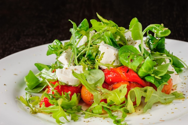 Warm salad with tomatoes, ruccola, spinach, cooked bell pepper and cheese