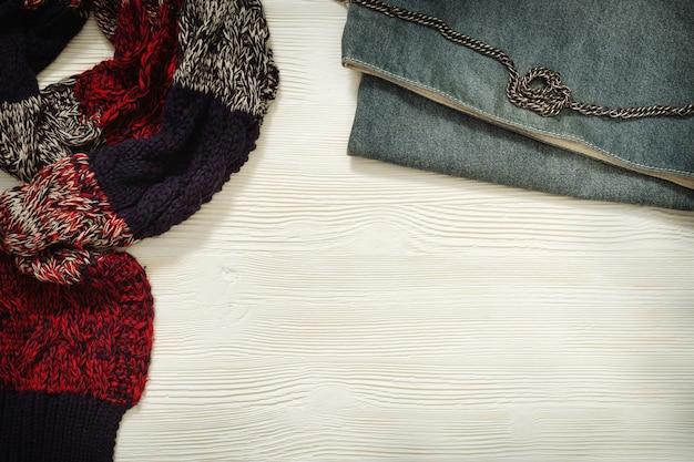 Теплый шарф с клетчатым рисунком, маленький джинсовый клатч на белом деревянном. женские аксессуары. модные повседневные наряды. ретро тонированное. квартира лежала. вид сверху.