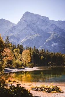 Теплый пейзаж озера, окруженного лесом и горами в яркий осенний день