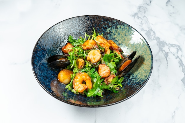 Warm seafood salad in a stylish black bowl on a marble table. scallop salad. mussels, shrimps in sweet and sour sauce. healthy and balanced food for dieting.