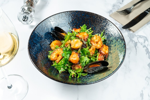 Warm seafood salad in a stylish black bowl on a marble table. scallop salad. mussels, shrimps in sweet and sour sauce.