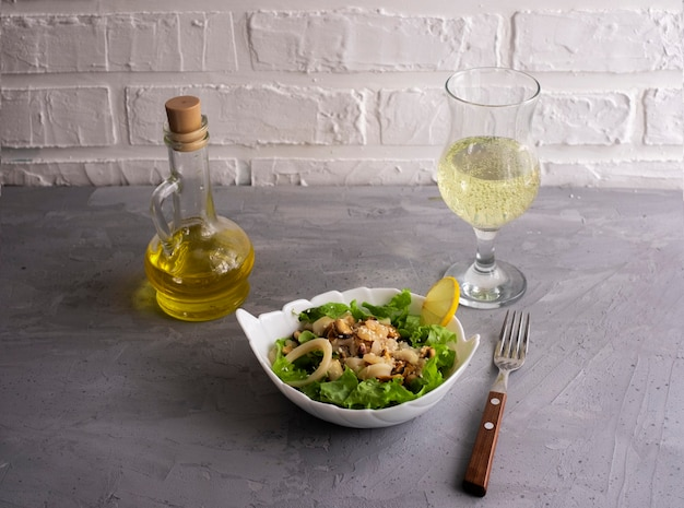 Warm seafood salad with green lettuce leaves with young white wine and olive oil