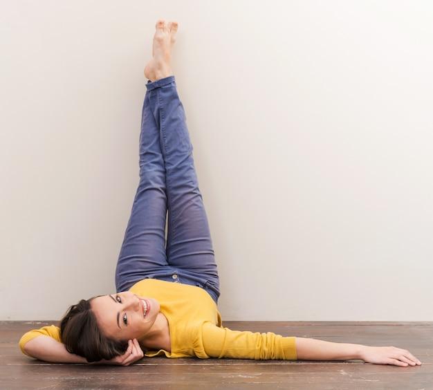 やさしい微笑み。カメラを見て、床に横になり、壁に彼女の足を傾けながら笑っている美しい若い女性
