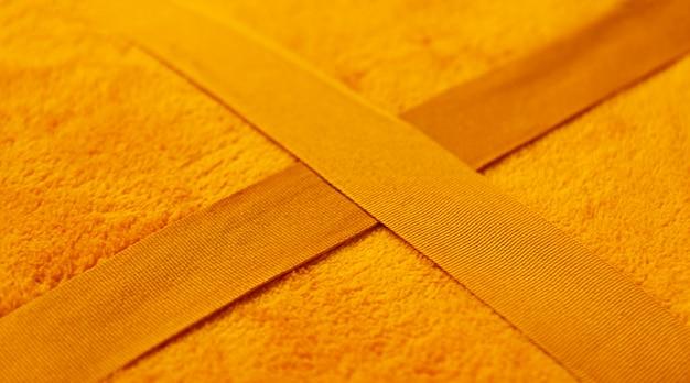 温かみのある柔らかな黄色のチェック柄の表面をクローズアップ。合成繊維の生地の質感。