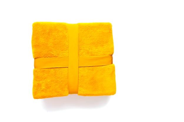 白い背景の上のリボンで結ばれた暖かい柔らかい黄色の格子縞。合成繊維のテクスチャ。
