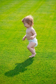 Warm spring time in the park baby in beautiful spring green field first step