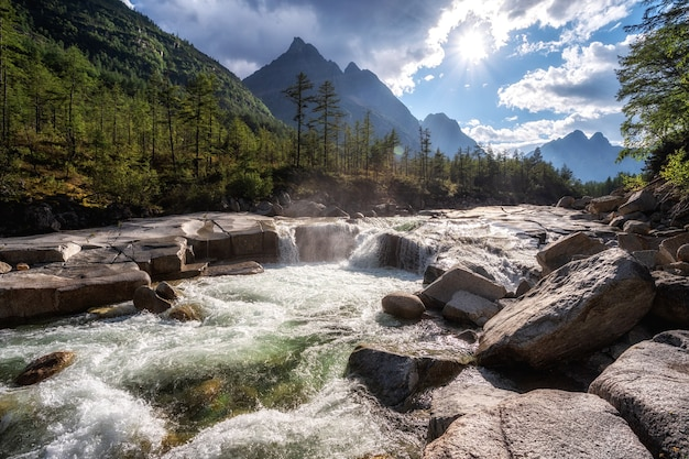 On a warm, summer and sunny day, a mountain river flows over the smooth stones washed over the years