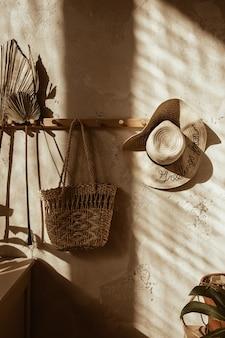壁に暖かい日光の影。自由奔放に生きるスタイルのモダンな家のインテリアデザイン。コンクリートの壁に対するわらと籐の装飾。