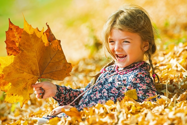 Warm sunny weather. smiling kid over autumn natural background. playing in the autumn park. children play outdoors.