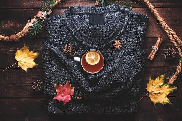 暖かいセーター、松ぼっくり、レモン、シナモン、アニスの星と秋のカエデの葉と熱いお茶のマグカップ。秋の服と飲み物。秋のコンセプト。