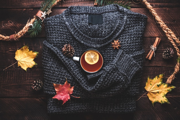 Warm sweater, pine cones, a mug of hot tea with lemon, cinnamon and aniseed stars and autumn maple leaves. autumn clothes and drinks. autumn concept.