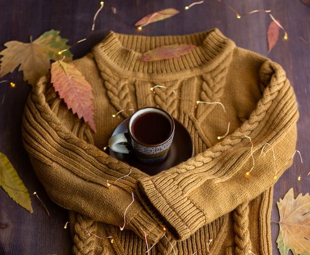 Теплые рукава свитера обнимают чашку кофе, осенний натюрморт с кофе и желтыми листьями и гирляндами