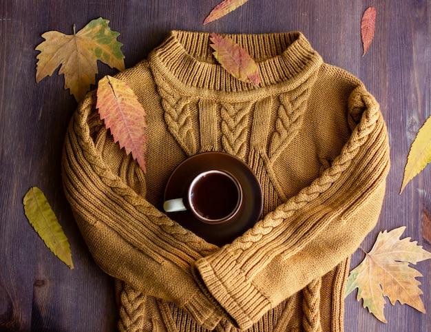 Теплые рукава свитера обнимают чашку кофе, осенний натюрморт с кофе и желтыми листьями
