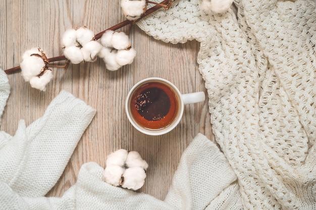 暖かいセーターとカップティー。暖かい色合いの居心地の良い静物。秋冬のコンセプトです。