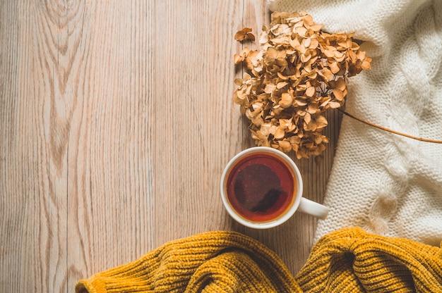 Теплые свитера и чашка чая. уютный натюрморт в теплых тонах. осенне-зимняя концепция.