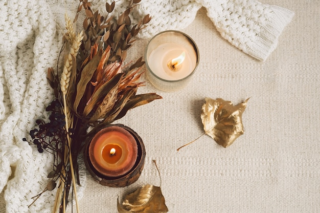 Warm sweaters, candles and dried flower bouquet