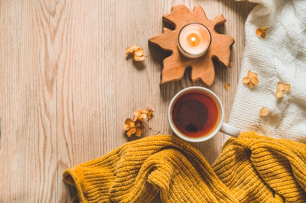 Warm sweaters and cup tea. cozy still life in warm shades. autumn winter concept.