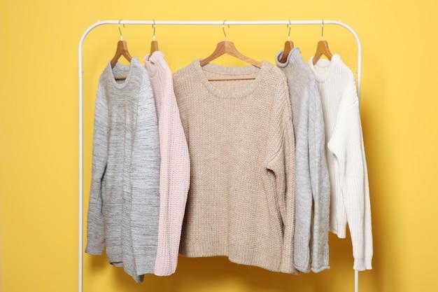 Теплые свитера на вешалке на цветном фоне