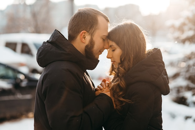 Warm and tender hugs of a couple in love in the cold winter season