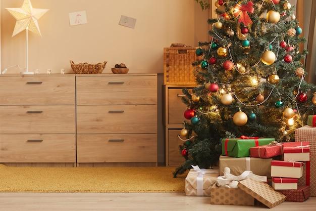 Теплое фоновое изображение украшенной елки в уютном домашнем интерьере, копия пространства