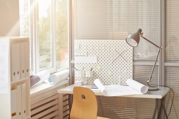 日光に照らされたエンジニアの職場の暖かい色調の背景画像、