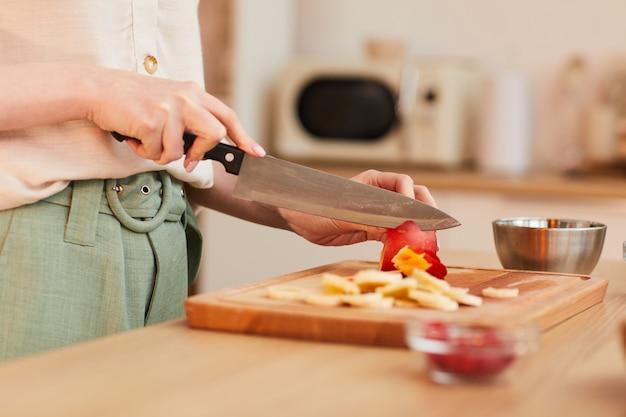 キッチンで健康的な朝食をしながら果物を切る認識できない女性の暖かいトーンのクローズアップ