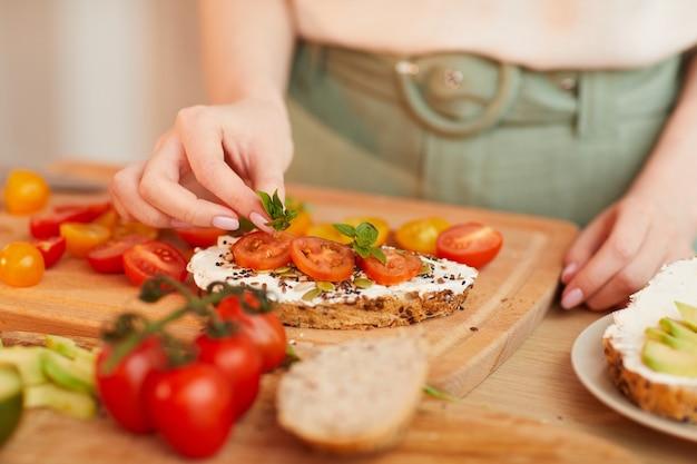 チェリートマトと全粒粉パンで健康的な朝食サンドイッチを準備している認識できない女性の温かみのある色調のクローズアップ