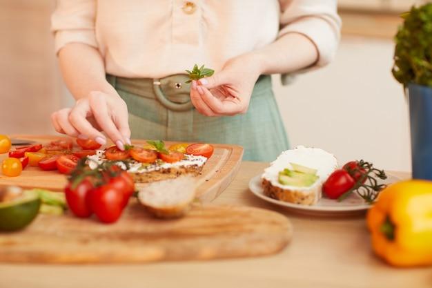 居心地の良いキッチンのインテリアで朝食に健康的なトマトサンドイッチを準備している認識できない女性の温かみのある色調のクローズアップ