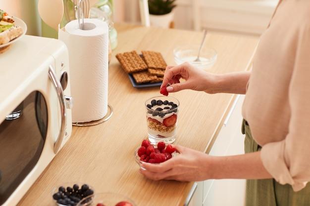 Теплый крупный план неузнаваемой молодой женщины, готовящей парфе из йогурта со свежими ягодами и мюсли, готовя здоровый завтрак утром