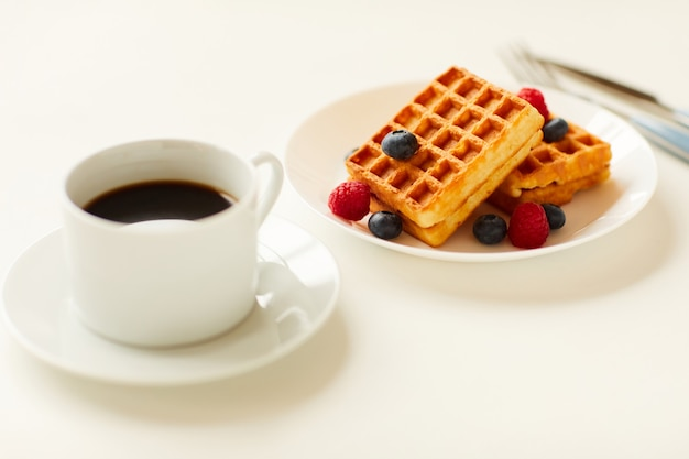 Warm-toned close up of sweet dessert waffles with berry topping next to cup of black coffee