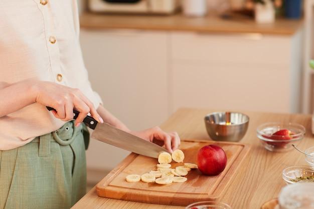 인식 할 수없는 여자 절단 과일의 따뜻한 톤의 근접 촬영 부엌에서 건강한 아침 식사를 만드는 동안