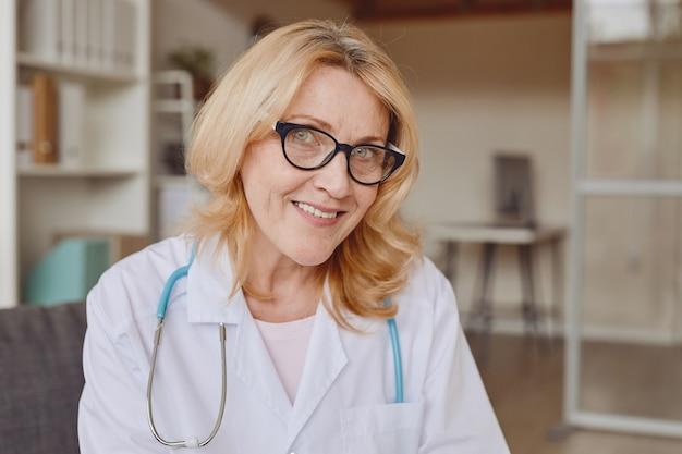 현대 병원에서 작업하는 동안 카메라에 미소 성숙한 여성의 따뜻한 톤의 머리와 어깨 초상화, 복사 공간