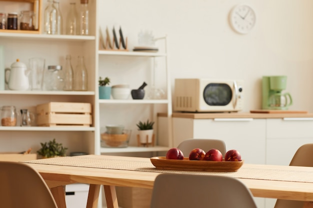 Warm-toned kitchen interior with minimal design and wooden table in foreground