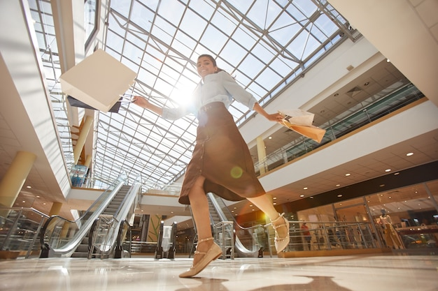 Теплые тона под низким углом портрет счастливой молодой женщины, прыгающей в торговом центре и держащей хозяйственные сумки, копировальное пространство