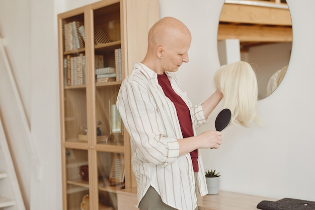 Warm-toned portrait of bald adult woman brushing wig while standing by mirror in modern home interior, alopecia and cancer awareness, copy space