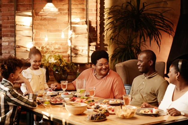 Warm toned portrait of big africanamerican family sitting at table outdoors and enjoying dinner toge...