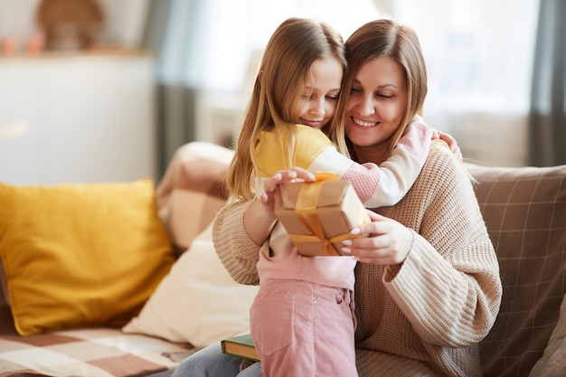 Warm-toned portrait of cute girl hugging mom after giving gift for birthday or mothers day, copy space