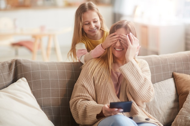 Warm toned portrait of cute girl playing peek a boo with mom while surprising her on mothers day, copy space