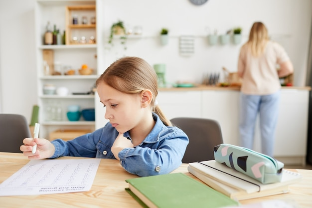 Warm-toned portrait of cute little girl doing homework while sitting at desk in cozy interior with mother in background, copy space